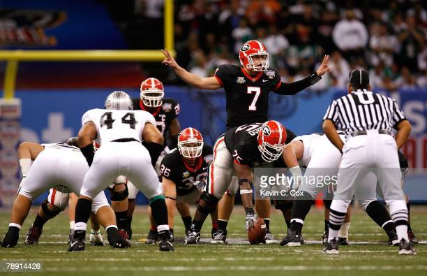 Matthew Stafford of the Georgia Bulldogs calls out signals at the line of scrimmage behind center Fernando Velasco against the Hawai'i Warriors...