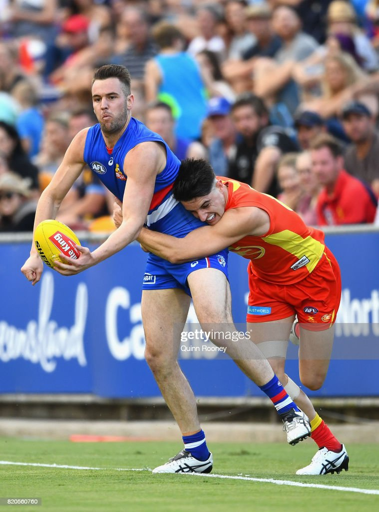 Matthew Suckling of the Bulldogs handballs whilst being tackled by Brayden Fiorini of the Suns during the round 18 AFL match between the Western Bulldogs and the Gold Coast Titans at Cazaly's Stadium on July 22, 2017 in Cairns, Australia.