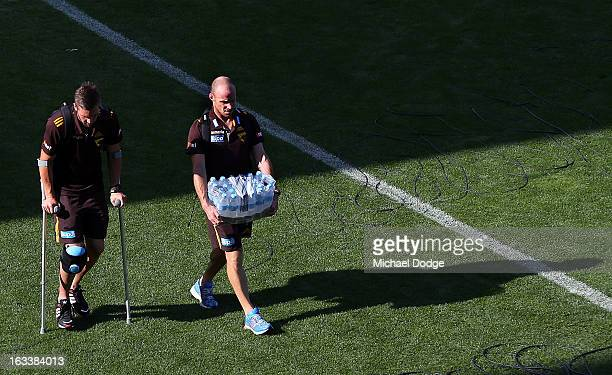 Matthew Suckling of the Hawthorn Hawks walks to the bus on crutches with fitness coach Andrew Russell after sustaining a right leg injury during the...