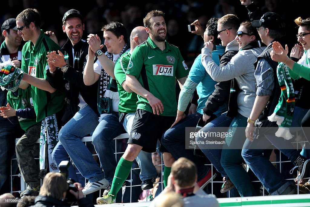 Matthew Taylor of Muenster celebrates on top of the fence after the 3. Liga match between Preussen Muenster and Karlsruher SC at Preussenstadion on April 20, 2013 in Muenster, Germany.