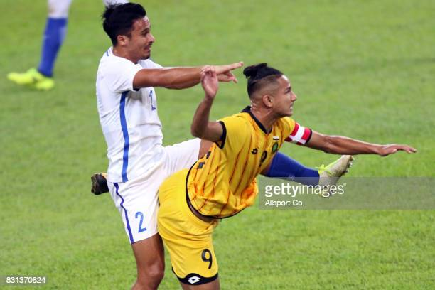 Matthew Thomas of Malaysia battles Faiq Jefri of Brunei during the preliminary round Group A football competition between Malaysia and Brunei at the...