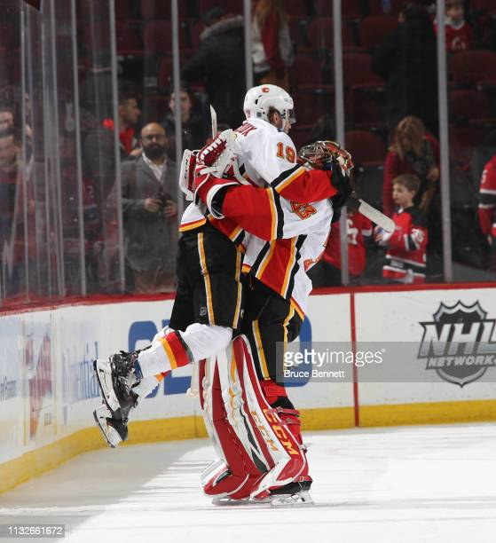 Matthew Tkachuk and David Rittich of the Calgary Flames celebrate their 21 victory over the New Jersey Devils at the Prudential Center on February 27...