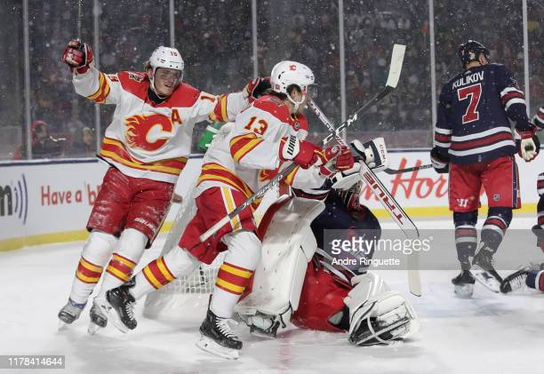 Matthew Tkachuk and Johnny Gaudreau of the Calgary Flames celebrate after a second period goal scored by teammate Elias Lindholm on Connor Hellebuyck...