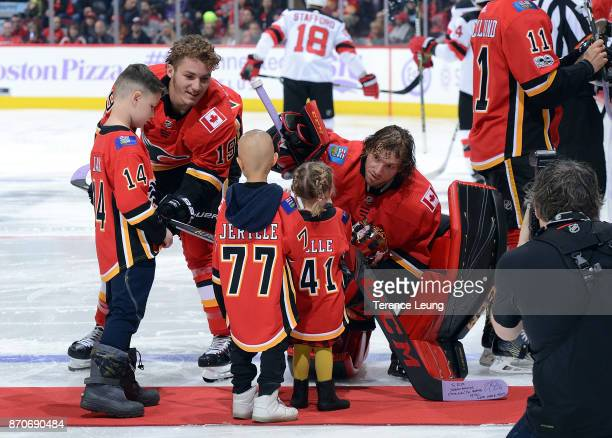 Matthew Tkachuk and Mike Smith of the Calgary Flames present their sticks to young fans for Hockey Fights Cancer before an NHL game against the New...