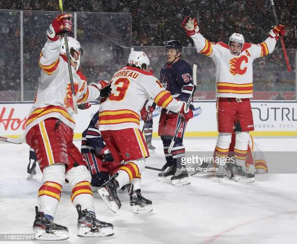 Matthew Tkachuk, Johnny Gaudreau and Sean Monahan of the Calgary Flames celebrate after a second period goal scored by teammate Elias Lindholm on the...