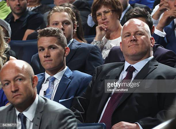 Matthew Tkachuk left looks on from his seat with father Keith prior to being selected sixth overall by the Calgary Flames during round one of the...