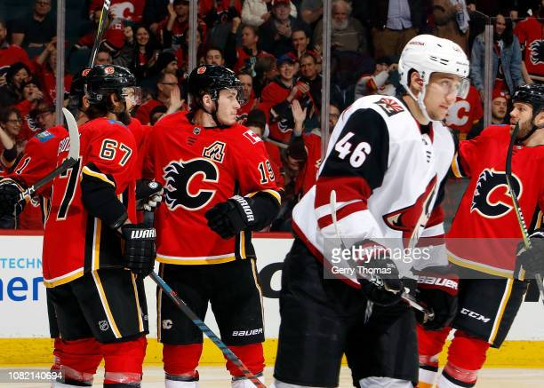 Matthew Tkachuk Michael Frolik and Dalton Prout of the Calgary Flames celebrate a goal against the Arizona Coyotes during an NHL game on January 13...