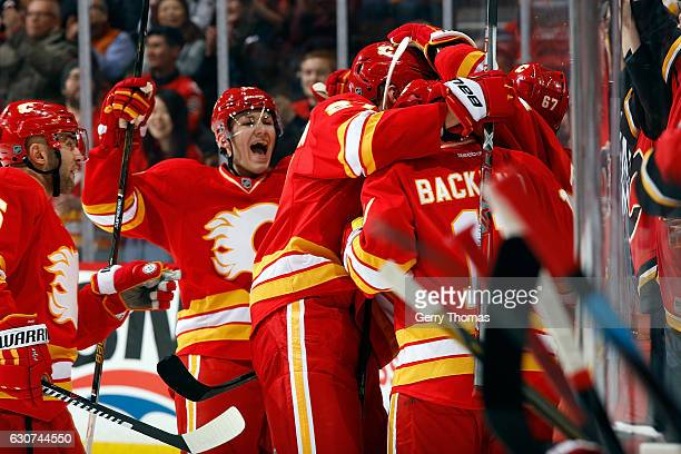 Matthew Tkachuk Mikael Backlund and teammates of the Calgary Flames celebrate a goal against the Arizona Coyotes during an NHL game on December 31...