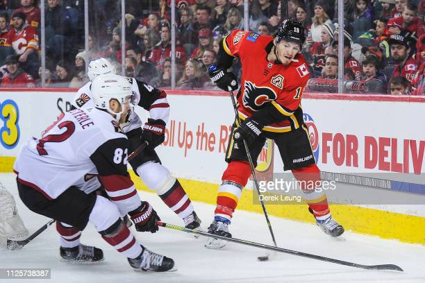 Matthew Tkachuk of the Calgary Flames carries the puck as Jordan Oesterle of the Arizona Coyotes looks to check him during an NHL game at Scotiabank...
