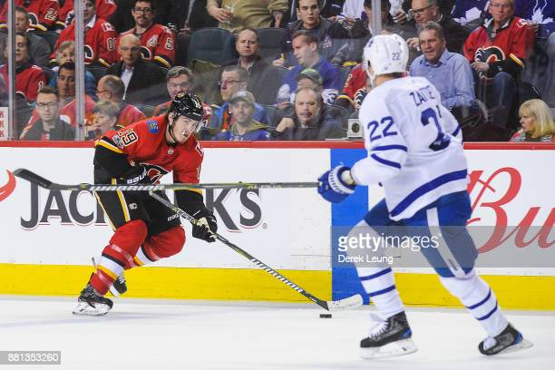 Matthew Tkachuk of the Calgary Flames carries the puck as Nikita Zaitsev of the Toronto Maple Leafs defends during an NHL game at Scotiabank...