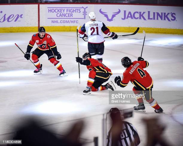 Matthew Tkachuk of the Calgary Flames celebrates after scoring the overtime winning goal against the Arizona Coyotes with Mikael Backlund and Rasmus...