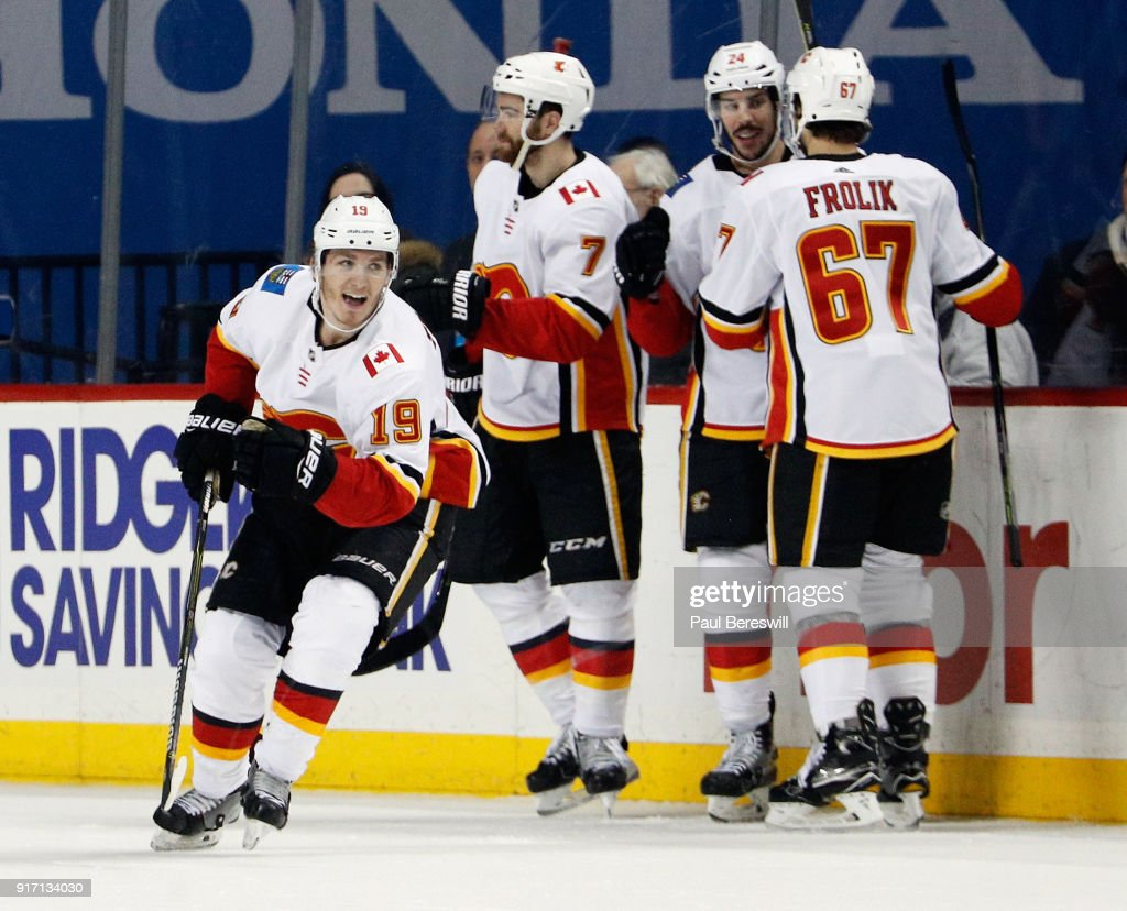 Matthew Tkachuk #19 of the Calgary Flames celebrates his game-winning goal against the New York Islanders with teammates TJ Brodie #7, Travis Hamonic #24 and Michael Frolik #67 at Barclays Center on February 11, 2018 in the Brooklyn borough of New York City. The Flames won 3-2.