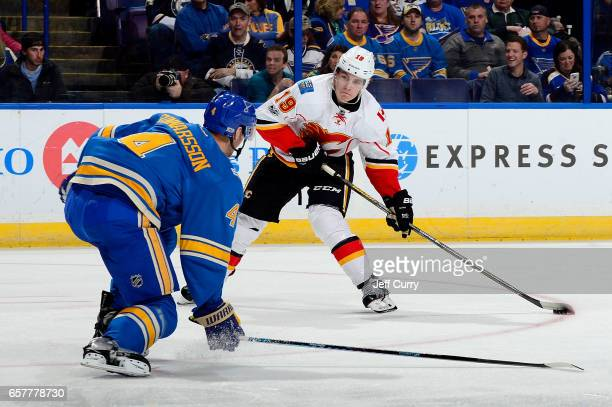 Matthew Tkachuk of the Calgary Flames handles the puck as Carl Gunnarsson of the St Louis Blues defends on March 25 2017 at Scottrade Center in St...