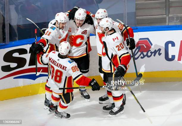 Matthew Tkachuk of the Calgary Flames is congratulated by teammates Andrew Mangiapane,Mikael Backlund,Oliver Kylington and Derek Forbort after...