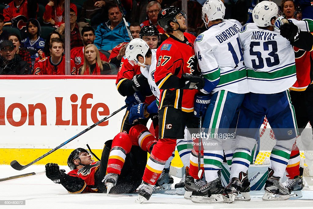 Matthew Tkachuk #17 of the Calgary Flames is knocked to the ice by Luca Sbisa #5 of the Vancouver Canucks during an NHL game on December 23, 2016 at the Scotiabank Saddledome in Calgary, Alberta, Canada.
