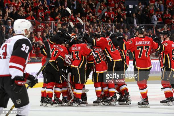Matthew Tkachuk of the Calgary Flames is mobbed by teammates after scoring the overtime winning goal against the Arizona Coyotes on November 5 2019...
