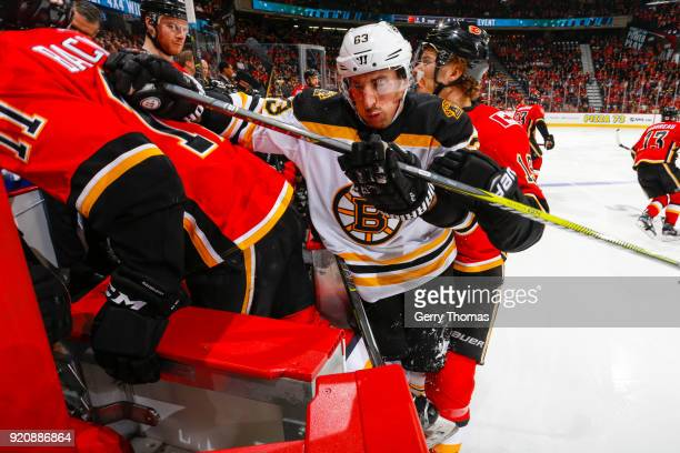 Matthew Tkachuk of the Calgary Flames pushes Brad Marchand of the Boston Bruins inside the Flames bench in an NHL game on February 19 2018 at the...