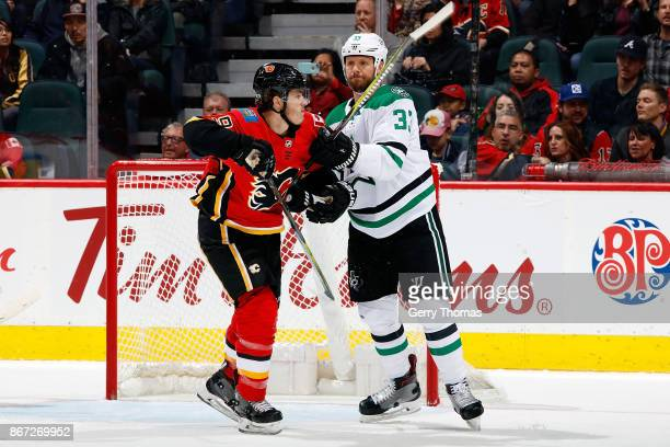 Matthew Tkachuk of the Calgary Flames skates against Marc Methot of the Dallas Stars during an NHL game on October 27 2017 at the Scotiabank...