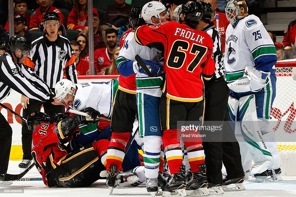 Matthew Tkachuk #17 of the Calgary Flames skates is knocked down to the ice by Chris Tanev #8 of the Vancouver Canucks during an NHL game on December 23, 2016 at the Scotiabank Saddledome in Calgary, Alberta, Canada.