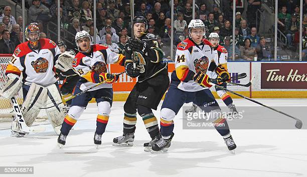 Matthew Tkachuk of the London Knights battles between Brett Neumann and Travis Dermott of the Erie Otters during game four of the OHL Western...