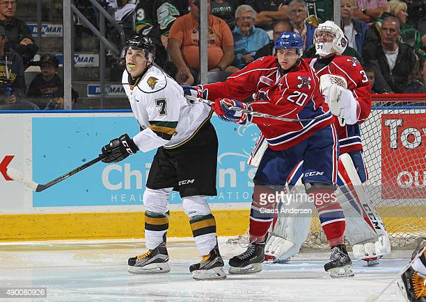 Matthew Tkachuk of the London Knights is checked by Cole Candella of the Hamilton Bulldogs in an OHL game at Budweiser Gardens on September 25 2015...