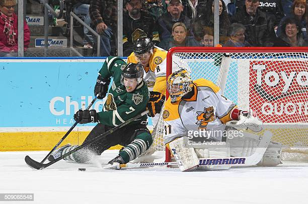 Matthew Tkachuk of the London Knights tries to elude the checking of Josh Jacobs of the Sarnia Sting to get a backhand shot on Charlie Graham during...