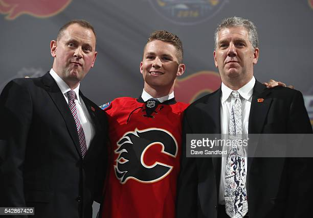 Matthew Tkachuk poses onstage with Calgary Flames team personnel after being selected sixth overall by the Calgary Flames during round one of the...
