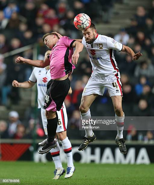 Matthew Upson of Milton Keynes Dons heads the ball away from Sam Hoskins of Northampton Town during The Emirates FA Cup Third Round Replay match...