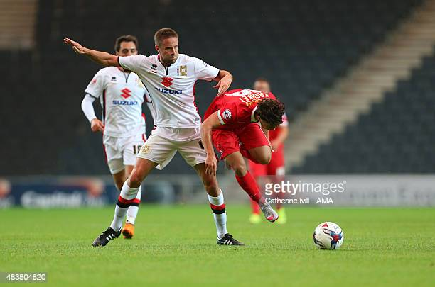 Matthew Upson of MK Dons fouls Scott Kashket of Leyton Orient during the Capital One Cup match between MK Dons and Leyton Orient at Stadium mk on...