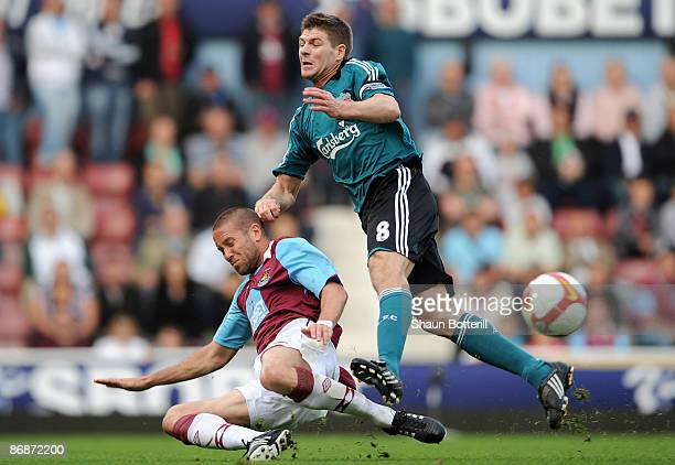 Matthew Upson of West Ham tackles Steven Gerrard of Liverpool during the Barclays Premier League match between West Ham United and Liverpool at Upton...