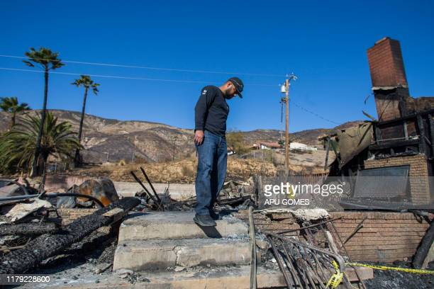 Matthew Valdivialooks for personal objects among the ashes of his home at Viento Way after being burned out by the Hillside fire in San Bernardino...