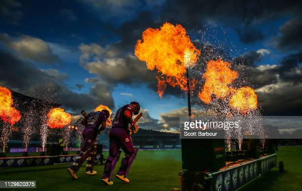 Matthew Wade and D'Arcy Short of the Hurricanes walk out to bat through flames during the Big Bash League semi final match between the Hobart...