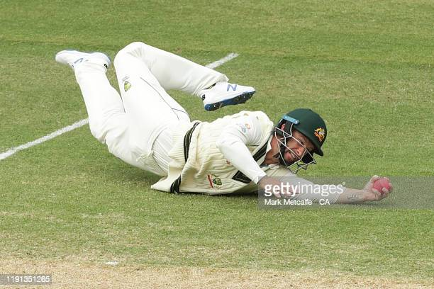 Matthew Wade of Australia dives to catch the ball during day four of the Second Test match in the series between Australia and Pakistan at Adelaide...