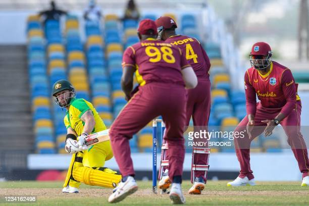 Matthew Wade of Australia hits a 4 as Kieron Pollard of the West Indies looks on during the 2nd ODI between West Indies and Australia at Kensington...