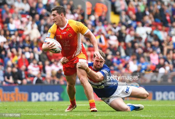 Matthew Whitley of Catalan Dragons is tackled by Danny Kirmond of Wakefield Trinity during the Wakefield Trinity v Catalans Dragons Betfred Super...