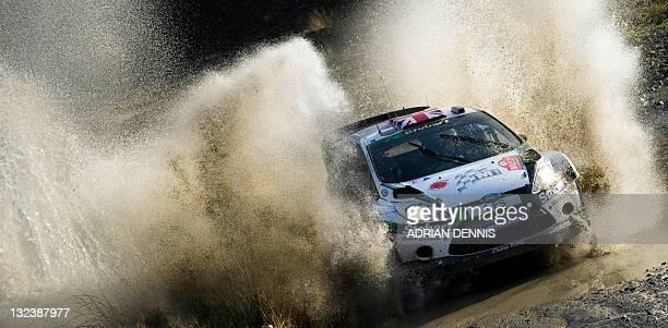 Matthew Wilson and codriver Scott Martin of Britain drives his MSport Stobart Ford Fiesta WRT car through a water splash on the Sweet Lamb stage...