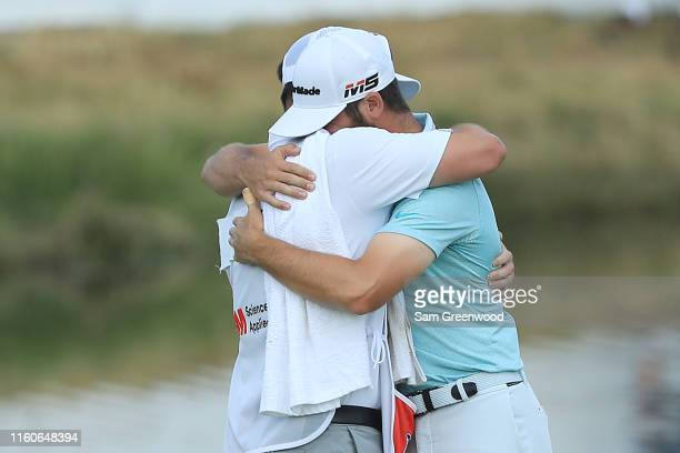 Matthew Wolff of the United States celebrates with his caddie on the 18th green after winning the 3M Open at TPC Twin Cities on July 07 2019 in...