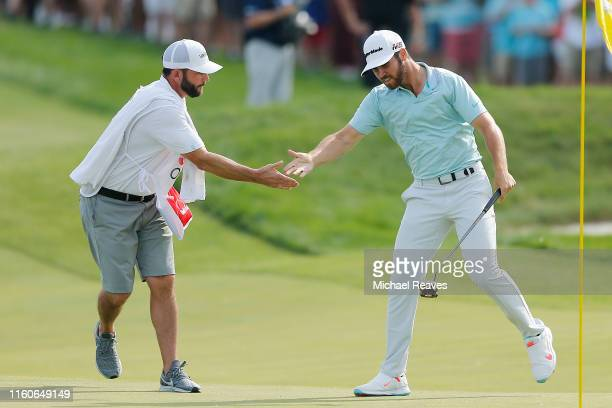 Matthew Wolff of the United States celebrates with his caddie Steve Lohmeyer after making a eagle putt on the 18th green to win the 3M Open at TPC...