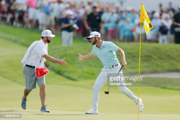 Matthew Wolff of the United States celebrates with his caddie, Steve Lohmeyer, after making a eagle putt on the 18th green to win the 3M Open at TPC...
