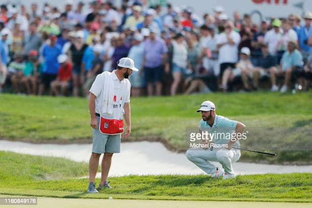 Matthew Wolff of the United States looks over a putt with his caddie Steve Lohmeyer on the 18th green during the final round of the 3M Open at TPC...