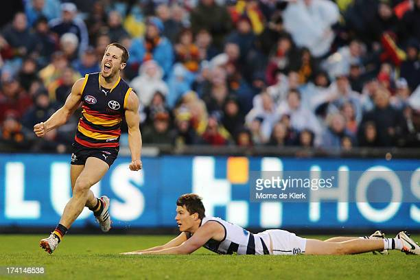 Matthew Wright of the Crows celebrates after kicking a late goal as Andrew Mackie of the Cats looks on during the round 17 AFL match between the...