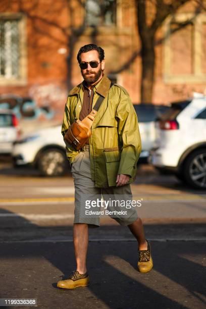Matthew Zorpas wears sunglasses a brown leather fanny pack shoulder strapped Fendi bag a green jacket a brown shirt shorts Fendi shoes outside Fendi...