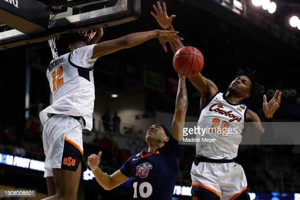 Matthew-Alexander Moncrieffe of the Oklahoma State Cowboys and Keylan Boone block the shot of Elijah Cuffee of the Liberty Flames during the first...