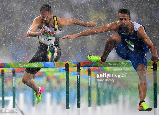 Matthias Buhler of Germany and Milan Trajkovic of Cyprus compete in the rain during the Men's 110m Hurdles Round 1 Heat 2 on Day 10 of the Rio 2016...