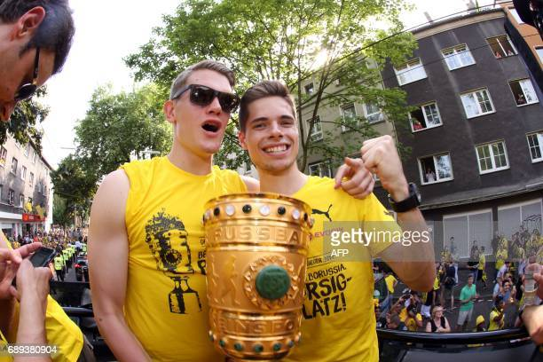 Matthias Dortmund's defender Matthias Ginter and Julian Dortmund's midfielder Julian Weigl hold the trophy as players arrive at Borsigplatz during...