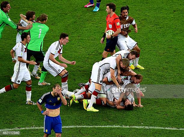 Matthias Ginter, Mario Goetze, Erik Durm, Benedikt Hoewedes, Per Mertesacker and teammates celebrate as a dejected Pablo Zabaleta of Argentina looks...