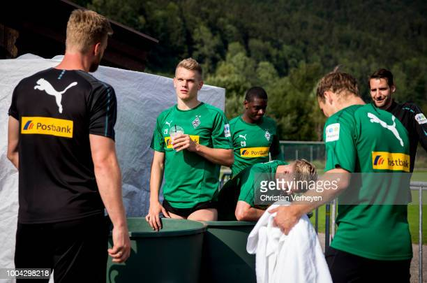 Matthias Ginter, Nico Elvedi and Mamadou Doucoure cool down in a ice box after a Training Session at Borussia Moenchengladbach Training Camp at...