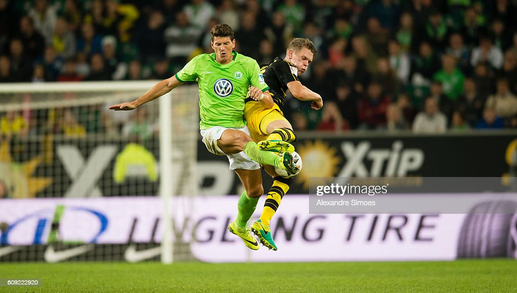 Matthias Ginter of Borussia Dortmund challenges Mario Gomez of VfL Wolfsburg during the Bundesliga match between VfL Wolfsburg and Borussia Dortmund at Volkswagen Arena on September 20, 2016 in Wolfsburg, Germany.