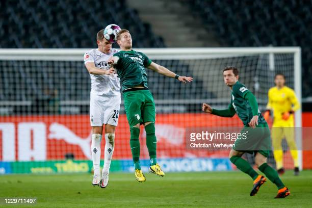 Matthias Ginter of Borussia Moenchengladbach and Andre Hahn of FC Augsburg battle for the ball during the Bundesliga match between Borussia...