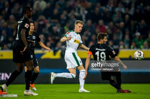 Matthias Ginter of Borussia Moenchengladbach and David Abraham of Eintracht Frankfurt battle for the ball during the Bundesliga match between...